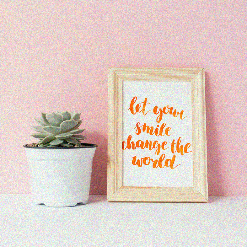 "Succulent in white pot and card with inspirational quote ""let your smile change the world"" in a wooden photo frame in front of pale pink pastel background"